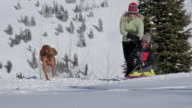 A mother and son sled on a sunny, winter day