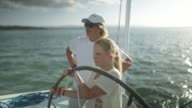 Mother and teen daughter at the wheel helm of sailing yacht