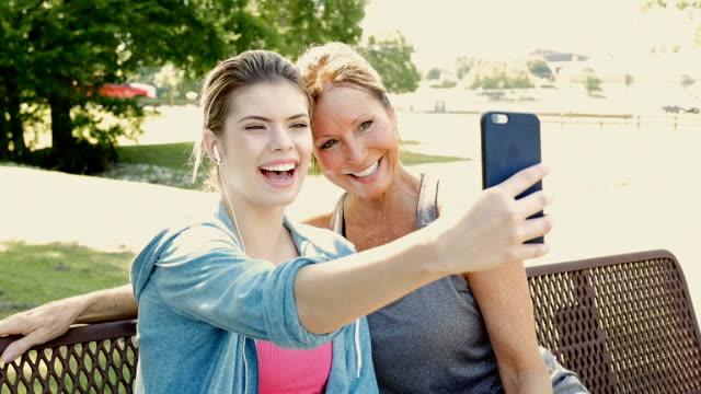 Mutter und Teen Tochter fotografieren Selfie zusammen draußen im park