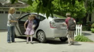 MS PAN Mother and three kids (9-11) getting out of car and unloading groceries from trunk, Encino, California, USA