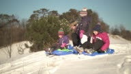 mother and three sisters on snowy hill with bobsleds