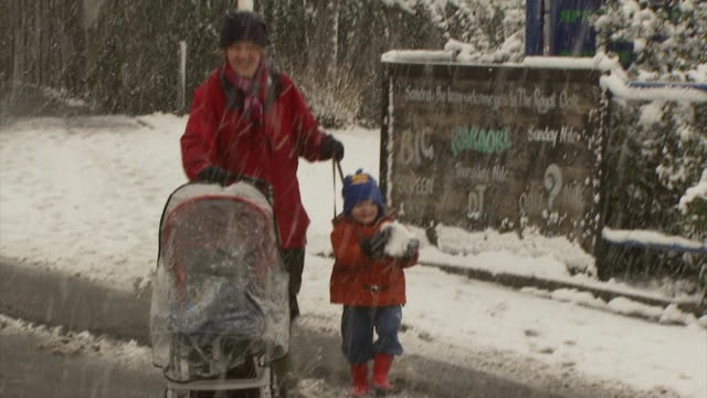 MS mother and toddler walking along snowy street, toddler has a large snowball, United Kingdom