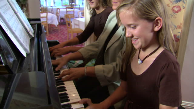 MS DS TD Mother and two daughters (11-17) playing piano together at home / Heber City, Utah, USA