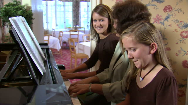 MS DS Mother and two daughters (11-17) playing piano together at home / Heber City, Utah, USA