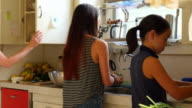 MS Mother and two daughters preparing dinner together in kitchen