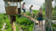 WS SLO MO. Mother and two daughters walk down steps from canopy lookout and explore Austin treehouse resort.