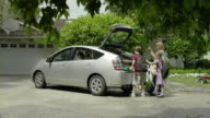 MS PAN Mother and two kids (9-11) loading bags into trunk and getting in car parked in driveway, Encino, California, USA