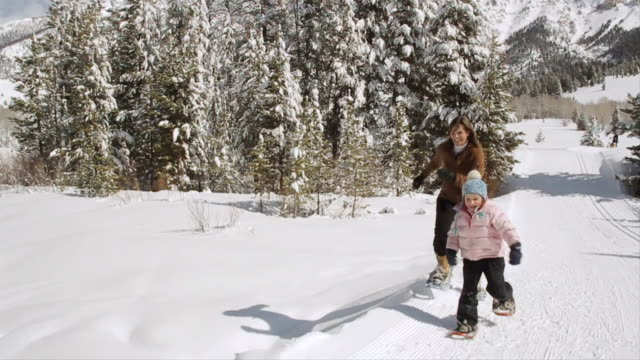 WS POV SLO MO Mother and young daughter racing and having fun on snowshoes / Sun Valley, Idaho, United States