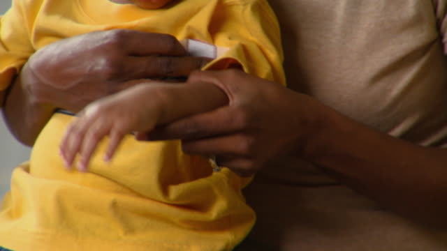 CU, TU, Mother applying bandage to son's arm (12-17 months), Richmond, Virginia, USA