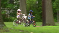 WS Mother arriving to giving boy a push on his bike as rides alongside girl on park bike path/ Fanwood, New Jersey
