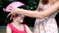 Mutter helfen, ihre Tochter mit Fahrradhelm.