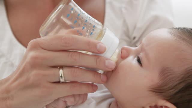 Mother bottle feeding baby girl