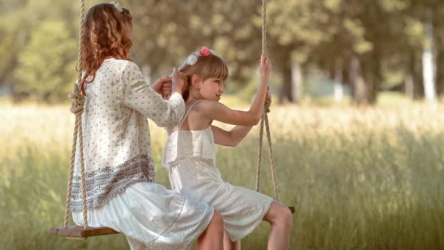 SLO MO Mutter Tochter Flechten Haare auf einer Schaukel