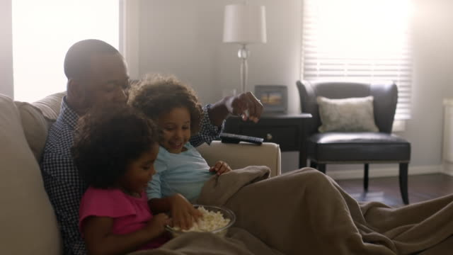 Mother bringing popcorn to family on sofa