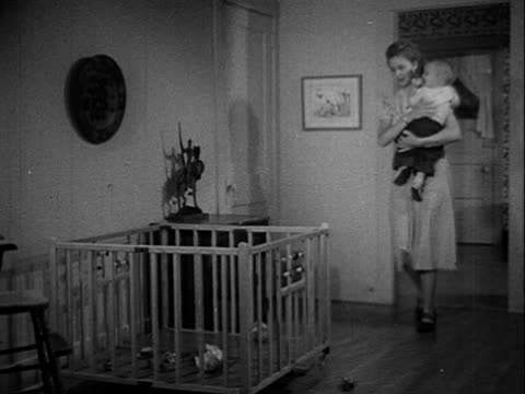 Mother carrying baby boy into a room placing into wooden play pen