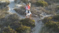 WS TD Mother carrying daughter (6-7) and walking from beach / Cape Town South Africa