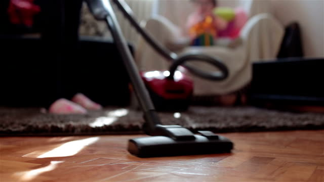 Mother cleaning room with vacuum cleaner