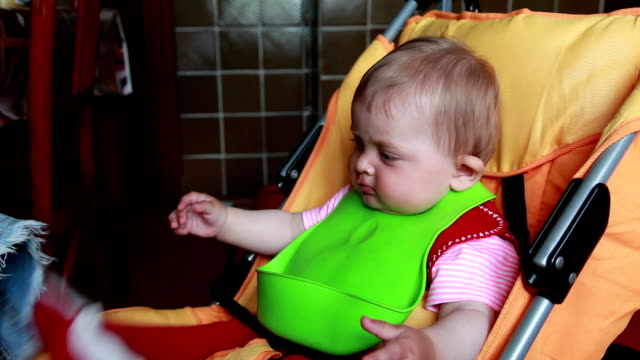 Mother cleans food leftovers from the baby clothes