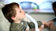 A mother comforts her little boy as he breathes near a nebulizer to inhale medicine.