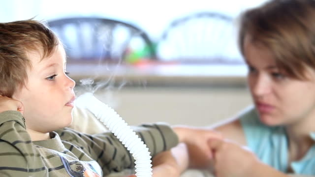 A mother comforts her little boy as he uses a nebulizer to inhale medicine.