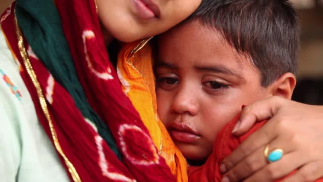 Mother consoling her crying son, Faridabad, Haryana, India