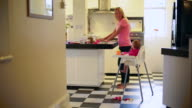 WS Mother cooking in the kitchen while baby watches.