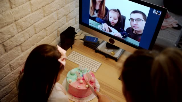 Mother cutting birthday cake while birthday girl talking with her abroad cousins on a video app