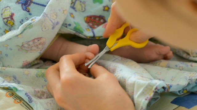Mother cutting nails of baby
