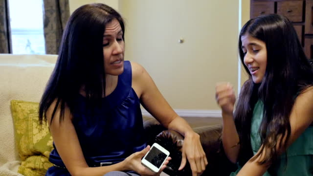 Mother discussing broken smartphone with her teenage daughter