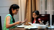 Mother eating dinner with her daughter in the home, Delhi, India