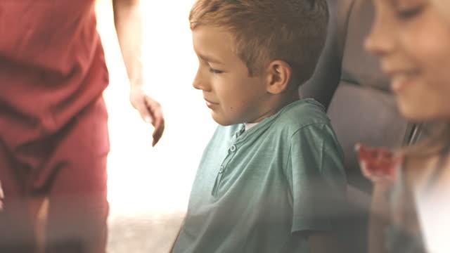 Mother fastening seat belt for children in car