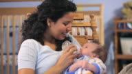 CU Mother feeding baby boy (2-5 months) from bottle in nursery room / Richmond, Virginia, USA.