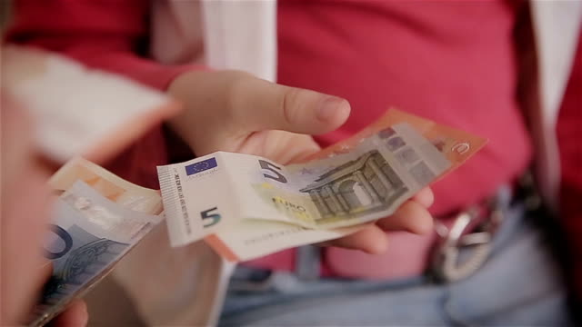 Mother gives daughter the money,human hands,close up