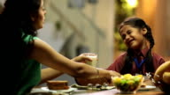 Mother giving a glass of milk to her daughter, Delhi, India