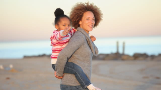 MS PAN Mother giving daughter (4-5) piggyback ride on Virginia Beach / Virginia, USA