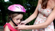 Mother Helping Child with cycling helmet.