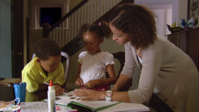 MS, mother helping daughter (4-5) and son (6-7) do homework at home, Westfield, New Jersey, USA