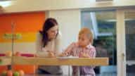 MS Mother helping daughter (10-11) in doing homework in kitchen / Kleinmachnow, Brandenburg, Germany