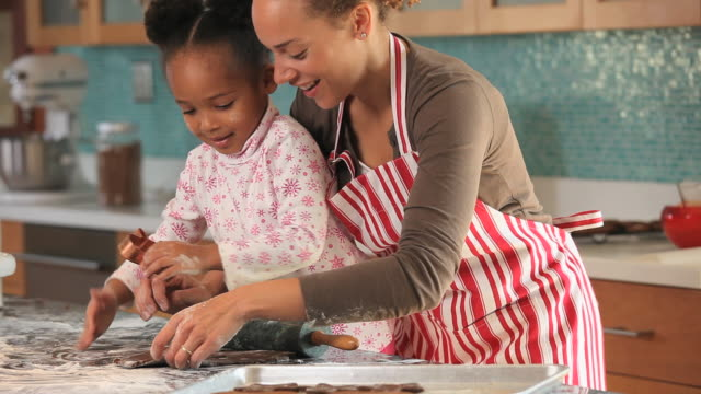 MS Mother helping daughter (4-5) make for gingerbread cookies in kitchen / Richmond, Virginia, USA