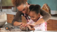 MS Mother helping daughter (4-5) rolling out dough for gingerbread cookies in kitchen / Richmond, Virginia, USA