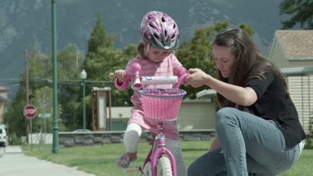Mother helping daughter to learn to ride a bike.