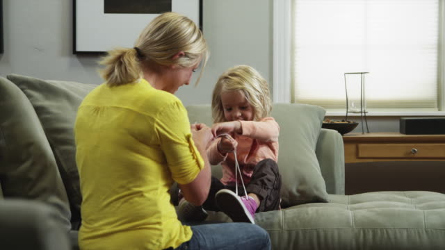 MS ZI Mother helping daughter (4-5) tying shoes on sofa / Orem, Utah, USA