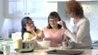 Mother helping down syndrome girls bake in kitchen