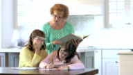 Mother helping down syndrome girls with homework