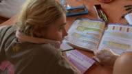 CU Mother helping girl doing school work at home / San Pedro de Atacama, Norte Grande, Chile