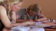 MS Mother helping girl doing school work at home / San Pedro de Atacama, Norte Grande, Chile