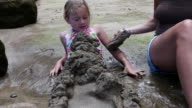 MS PAN Mother helping her daughter bury herself with sand from beach / Kauai, Hawaii, United States