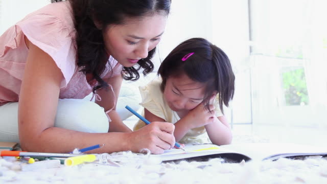 Mother helping her daughter with colouring