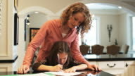 mother helping her daughter with her homework at the kitchen counter