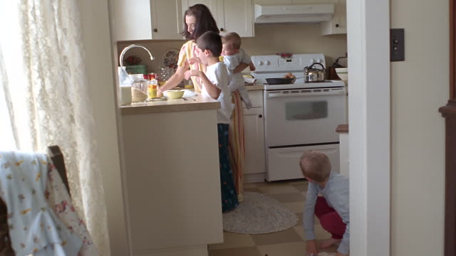 MS Mother helping son clean spilled cereal on kitchen floor while holding baby / Washington State, USA